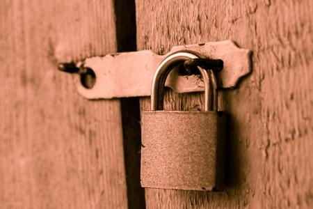Metal lock on the wooden door closeup photo