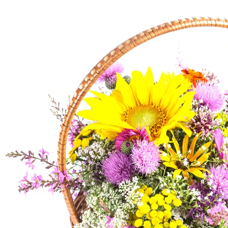Bouquet of wild flowers and sunflowers in basket isolated photo