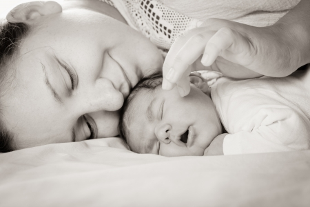 Sleep baby with mom, closeup faces photo