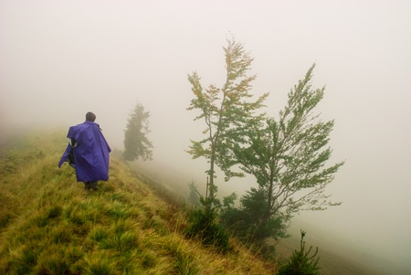 Lost man in a raincoat in mountains with fog, storm and rain Stock Photo - 15320980