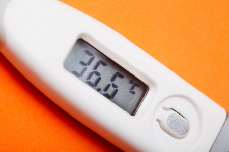 Electronic thermometer with 36,6 C closeup on the orange backgroun photo