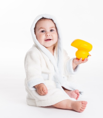 Baby in a bathrobe after a bath with yellow toy isolated photo