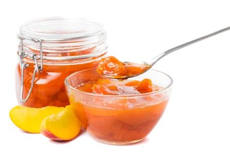 Tasty peach jam in glass jar with fruits over white
