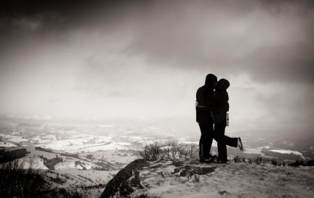 personas abrazadas: Dos personas en el pico de la monta�a se abrazan Foto de archivo