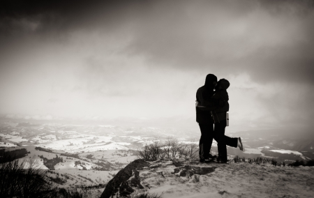 Two people at the peak of the mountain are hugging photo