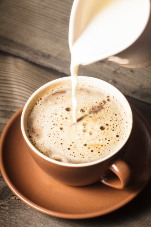Coffee in brown cup and milk on wood background closeup photo