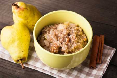 Oatmeal with pears and cinnamon and walnut on the wooden table Stock Photo - 16396867