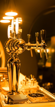 Beer taps in a bar for spilling drinks photo