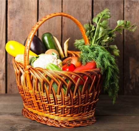 Basket with vegetables and fresh herbs on the wood background photo