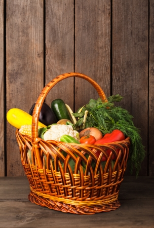 Basket with vegetables and fresh herbs on the wood background with copy space photo