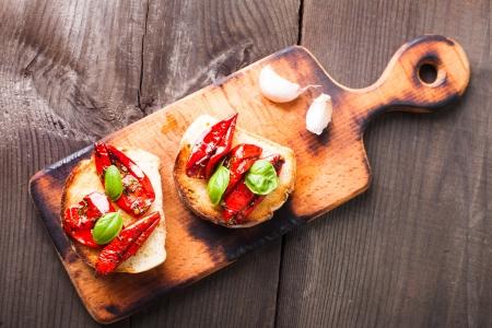 Bruschetta con tomates secados al sol, las hojas de albahaca y ajo