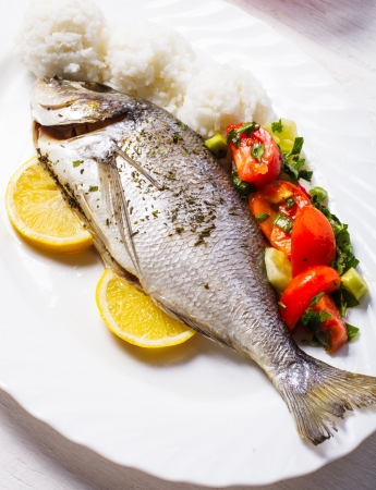 sparus: Baked dorado fish with rice and salad on the white plate Stock Photo