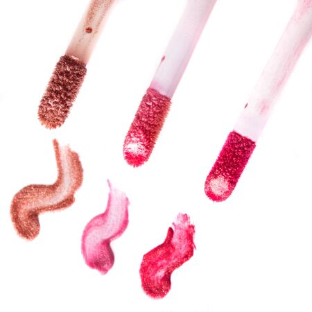 glitter gloss: Varuous smears of lip gloss on white background