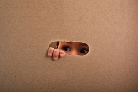 out of the box: A small child looking out the gap of craft box Stock Photo