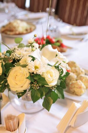 Flower decorations on the banquet table, prepared for event party or  wedding photo