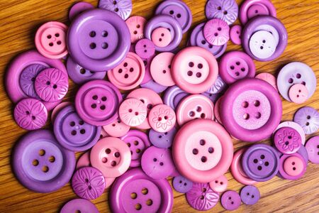 A lot of pink and purple sewing buttons closeup photo