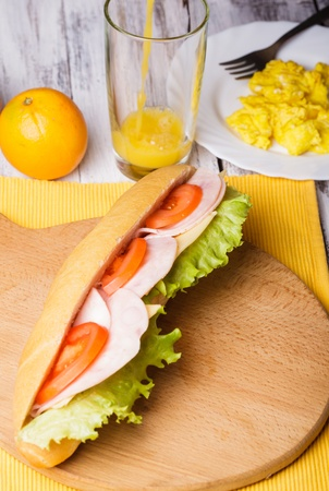 Breakfast with a sandwich, orange juice and scrambled eggs photo