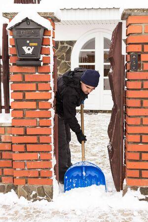Young man remove snow near the suburban house photo