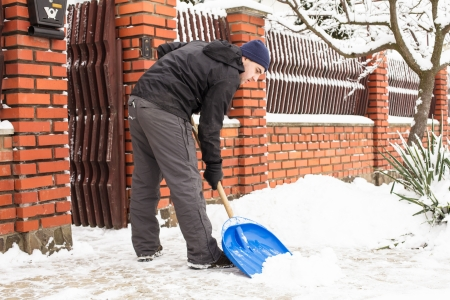 shoveling: Young man remove snow near the suburban house