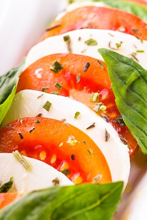 Caprese salad: slices of tomato and mozzarella cheese photo