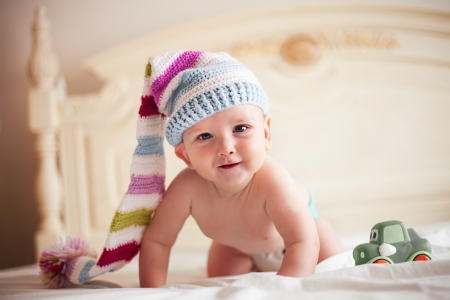 interested baby: Five-month baby in crochet hat on all fours is smiling Stock Photo