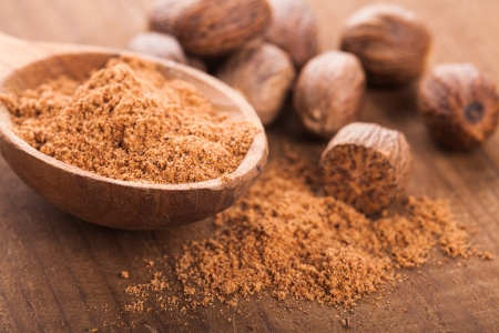 Ground nutmeg spice in the wooden spoon closeup photo