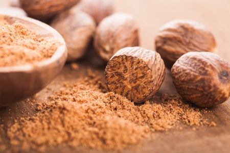 Ground nutmeg spice in the wooden spoon closeup Stock Photo