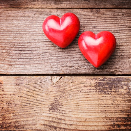 Two red hearts on old shabby wooden background with copy space photo