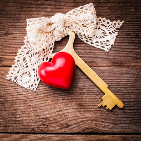 Old intage key and red heart. Key of my heart concept. Valentine's day greetings. photo