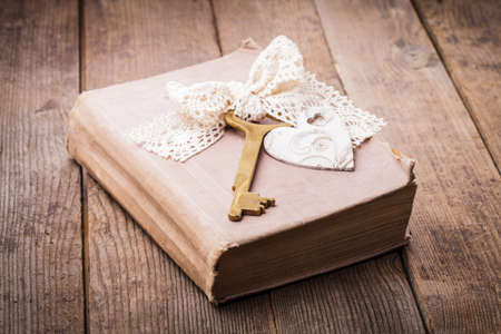 Old book with vintage key and wooden heart, memories concept photo