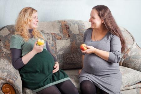 Zwei schwangere Frauen essen Obst und diskutieren Schwangerschaft