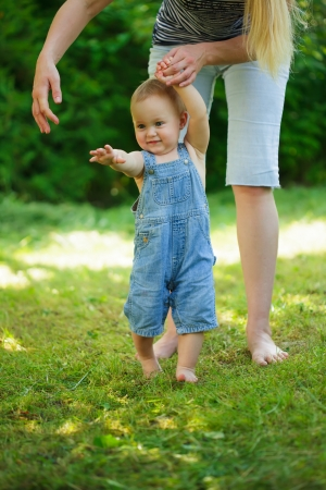 First steps of baby from mother on grass Stock Photo