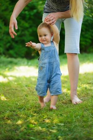Primeros pasos de bebé de la madre en hierba