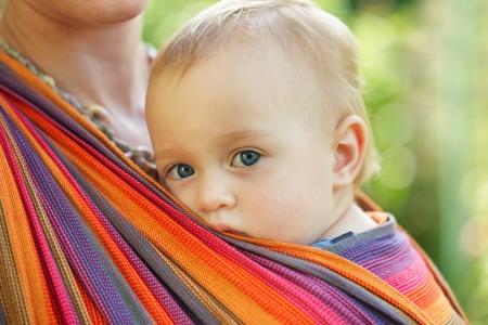 Bebé en honda mirando al aire libre. La madre lleva a su hijo. Foto de archivo