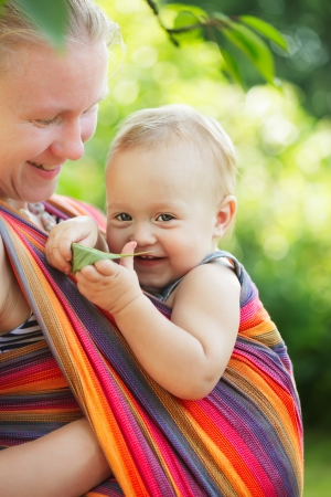Baby in sling outdoor. Mother is carrying her child and showing nature details photo