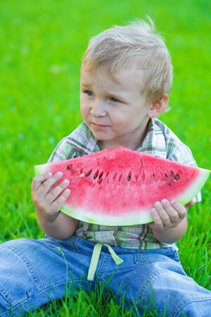 Kid with slice of watermelon, outdoors eating, picnic photo