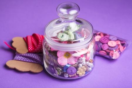 brads: Scrapbooking craft materials in glass bottle on violet background