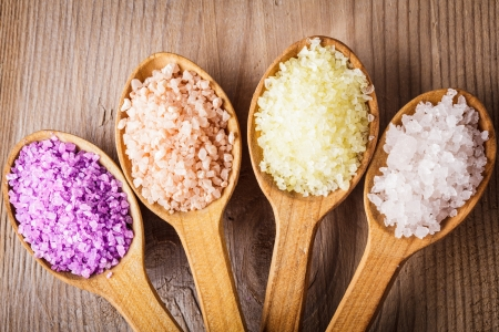 Various types of spa sea salt in wooden spoons closeup photo