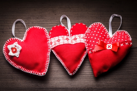 Sewed handmade red hearts on wooden background photo