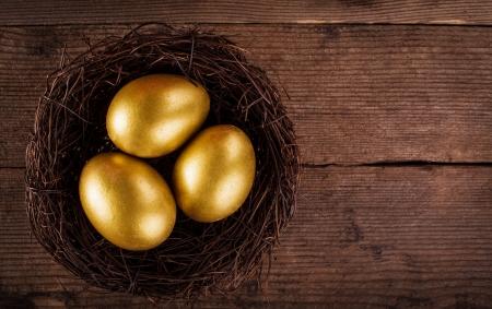 nido de pajaros: huevos de oro en el nido sobre fondo de madera con el texto de la copia