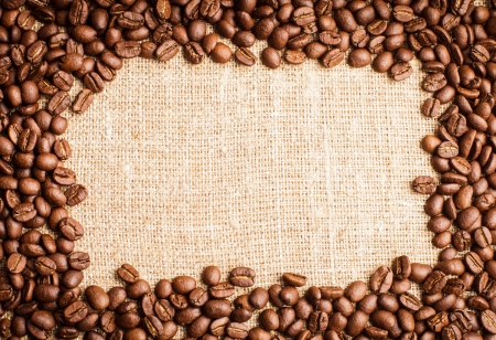 Spilled coffee beans frame over burlap textile photo