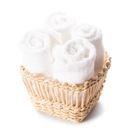 spa towels: White spa towels pile in a basket isolated