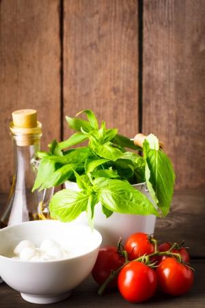 caprese salad: Ingredients for caprese salad over wooden wall, italian food Stock Photo