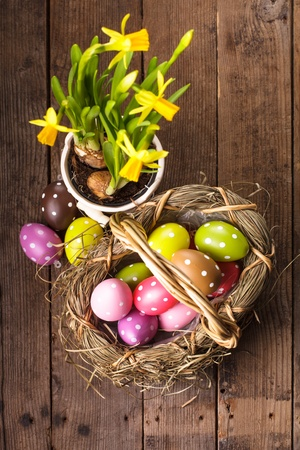 Colorful polka dot eggs in basket and daffodil flowers photo