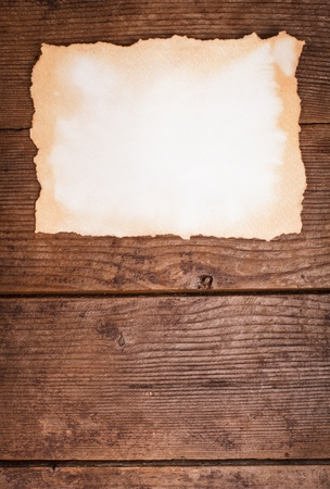 Empty aged paper on the wooden background photo