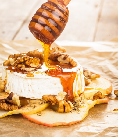 honey liquid: Baked camembert with apples dipped with honey and walnuts Stock Photo