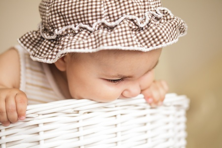 Eight month baby girl play with laundry basket photo