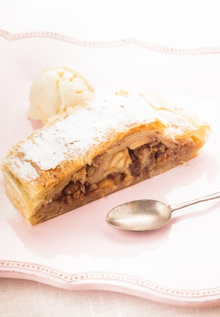 Apple strudel and ice cream ball on a pink plate photo