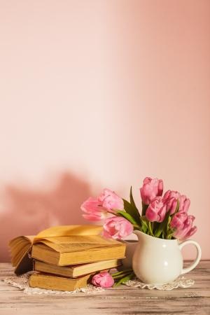 Poema de la naturaleza muerta con libros y tulipanes de color rosa con copia espacio. Día del Maestro.