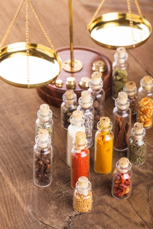 red gram: Little bottles with spices and scales on the table, vedic cuisine Stock Photo